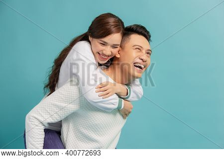Image Of Lovely Couple Having Fun While Man Piggybacking His Girlfriend Isolated Over Blue Backgroun