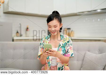 Happy Millennial Hispanic Teen Girl Checking Social Media Holding Smartphone At Home.