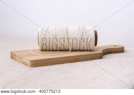 On A Wooden Kitchen Board Lies A Rope Wound On A Spool.