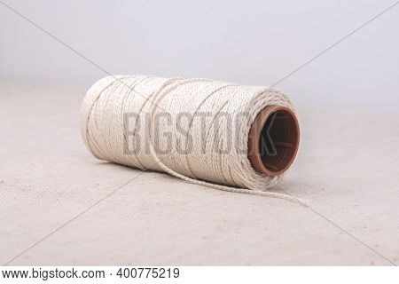 A Thick Rope Is Wound On A Plastic Spool And Rests On The Fabric.