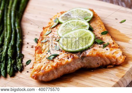 Salmon Fillet With Asparagus Ready To Eat On A Cutting Board.