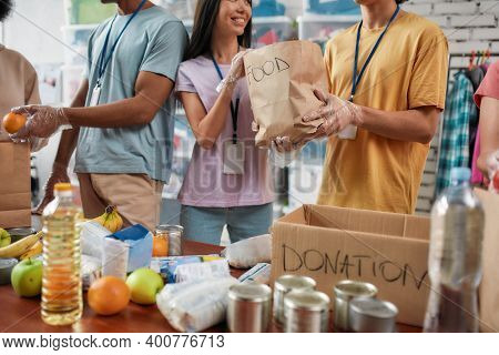 Cropped Shot Of Male And Female Volunteers Holding Paper Bag With Food While Packing Donation For Ne