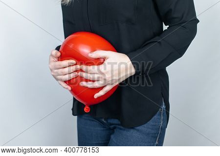 Bloating And Flatulence Concept. The Woman Holds A Red Balloon Near The Abdomen, Which Symbolizes Bl