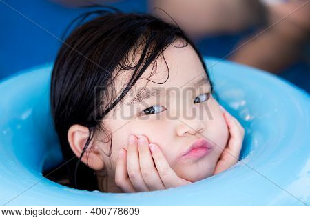 Head Shot. Kid Is Making A Sick Face. Child Puts Two Hands Under His Chin While Playing In The Water