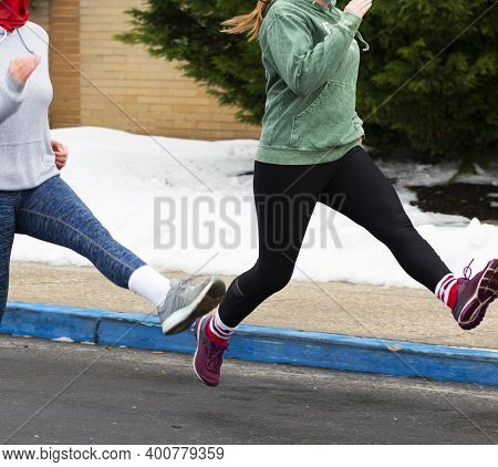 High School Girls Perfroming Running Drills In A Parking Lot Wearing Masks During 2020 Pandemic.