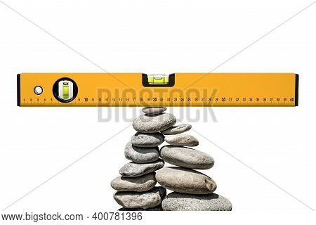 Closeup Of A Construction Spirit Level Or Bubble Level On A Pile Of Stones In Balance, Isolated On W