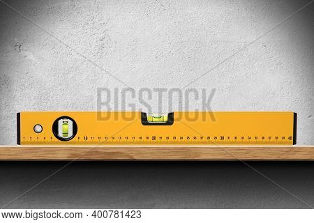 Closeup Of An Orange Bubble Level Or Spirit Level On A Wooden Shelf On White Wall.