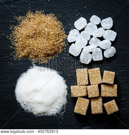 Assortment Of Sugar: White Sand, Candy Sugar, Brown Sugar Into Pieces And Brown Sugar On A Dark Back
