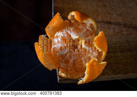 Peeled Tangerine On A Wooden Surface. Citrus Fruit. Peeled Tangerine Lies In Tangerine Peel