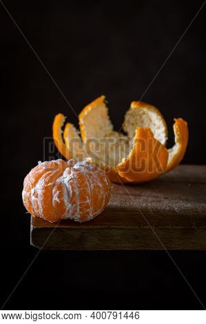 Peeled Tangerine On A Wooden Surface. Citrus Fruit. A Peeled Tangerine Lies Next To A Tangerine Peel
