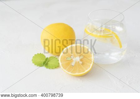 Transparent Glass With Pure Water, Lemon Slices, Mint Leaf ,  Whole Lemon And Half Of It Lie On  Lig
