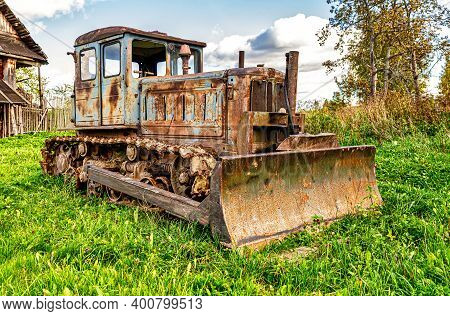 Old Soviet Arable Rusty Tractor On The Green Grass