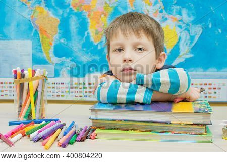 Preschooler Child Sits At The Table, Put His Hands And Head On The Books.learning Fatigue, Boredom.t