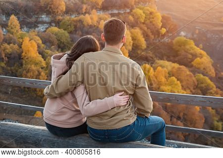 Guy And Long Haired Lady Hug Sitting On Large Log At Brown Wooden Handrails Against Hilly Landscape