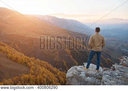 Man In Shirt Admires Sunrise Over Mountains With Coloured Forests And Fields Standing On Brown Rocky
