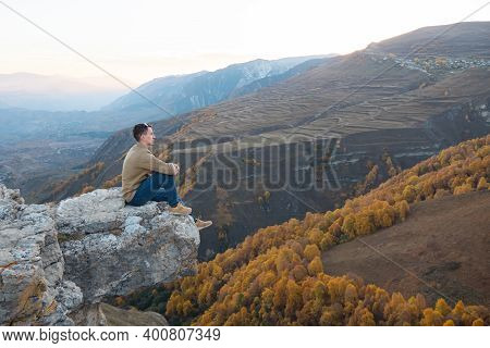 Guy In Brown Shirt And Blue Jeans Sits On Large Hilltop Rock Edge Against Orange Yellow Forests And