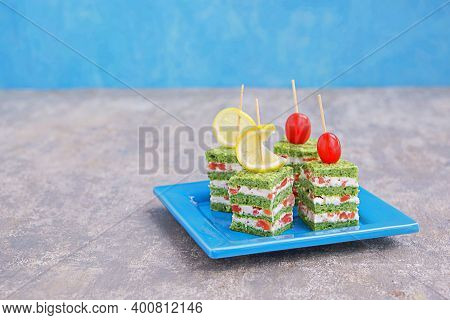 Snack, Savoury Spinach Biscuit Sandwices Or Canapes Layered With Cream Cheese And Salted Salmon On A