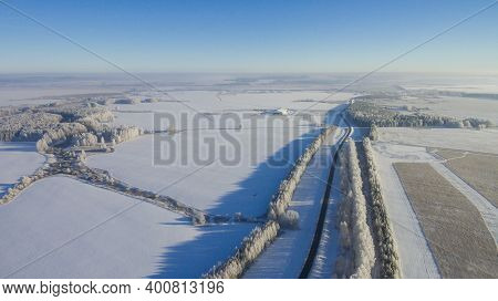 Winter Road Along The Fields Between Cities Aerial View From A Drone. Winter Landscape From A Drone.