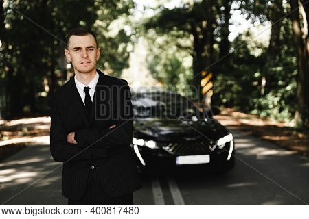 Young Successful Businessman Stands In Front Of His Expensive Car. Rich Young Guy. Rich Man. Car On