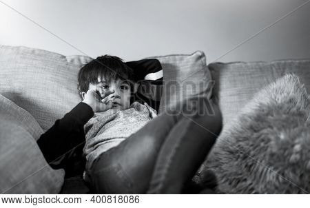 Kid Putting Finger In His Mouth.schoolboy Biting His Finger Nails While Watching Tv, Cinematic Portr