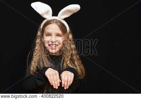 Young Girl On A Black Background With White Ears Of A Hare On Her Head. She Folded Her Hands Like A