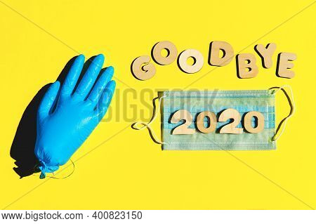 Words Goodbye 2020 From Wooden Letters, Inflated Medical Glove Waving Bye-bye And Facemask On A Yell
