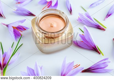 Saffron Flowers And Cosmetic Cream On A White Background. Cream With Saffron Extracts.
