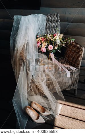 Wedding Bouquet, Veil And Shoes Of The Bride Are On A Chair