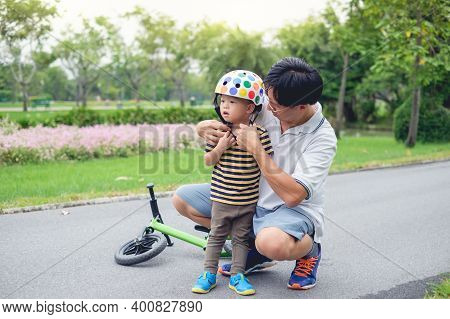Young Father Put Helmet On Cute Little Asian 2 Year Old Toddler Baby Boy Child, Dad And Son Having F