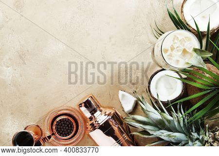 Pina Colada Cocktail On Sand Beige Background With Tropical Fruits And Bar Tools, Summer Relaxation