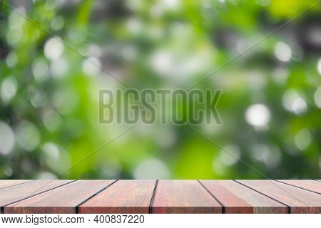 Wood Perspective On Blur Green Bokeh Of Leave In Spring Background. Copy Space For Add Text Presenta
