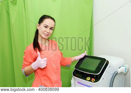 A Young Woman In A Medical Gown Near A Modern Apparatus Shows A Thumb Up. The Concept Of A Medical E
