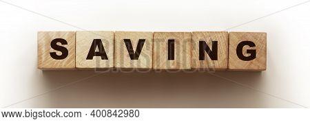 Saving Word Written In Wooden Cubes. Business Financial Concept