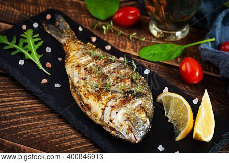 Grilled Dorado Fish On Wooden Background. Roasted Seafish With Spice And Herbs