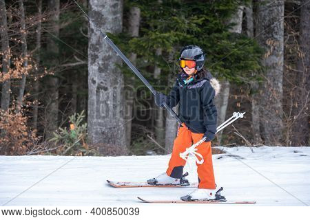 Skiing In The Snow. One Asian Girl Sitting On Ski Lift By Grabbing The Rope And Holding Ski Sticks.