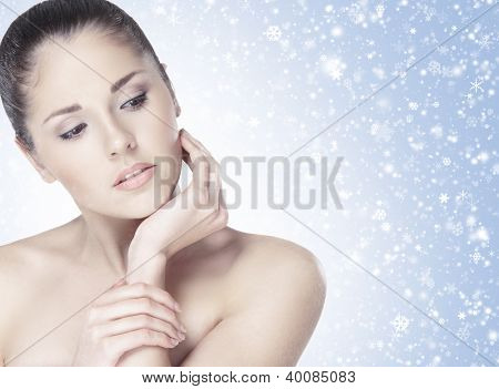 Portrait of young attractive brunette over winter background