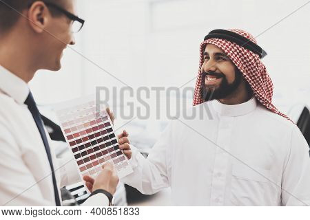 Arabic Man At Car Dealership. Salesman Is Showing Color Palettes For New Cars.
