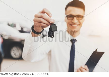 Male Seller Shows Keys To The Camera Of A New Car. The Seller In A Shirt And Tie Stands In A Car Dea