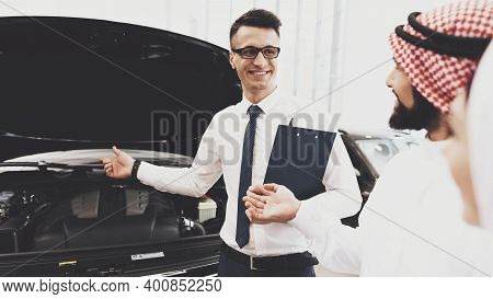 Arabic Man At Car Dealership. Salesman Is Showing Engine Of New Car To Man And His Wife.