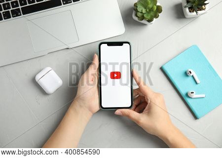 Mykolaiv, Ukraine - July 10, 2020: Woman Holding Iphone 11 With Youtube App On Screen At Table, Top