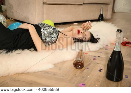 Woman Sleeping On Floor In Messy Room After New Year Party