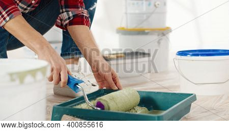 Young Beautiful Caucasian Cheerful Woman In Good Mood Preparing Paint For Painting Walls In New Apar