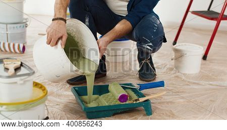 Close Up Of Caucasian Young Handsome Man Pouring Green Olive Paint Preparing For Painting Walls In H