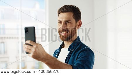 Close Up Of Happy Handsome Caucasian Male Talking On Video Chat Online On Smartphone While Renovatin