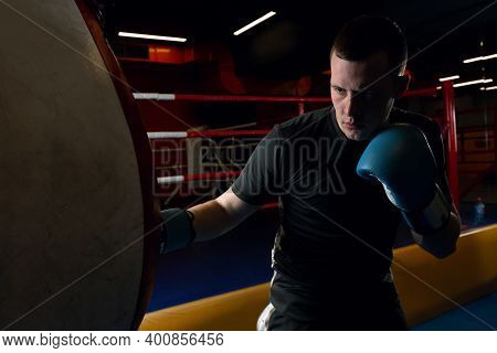 A Young Athlete In Black Uniforms And Blue Boxing Gloves During A Boxing Training Practice Works Out