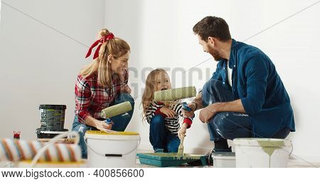 Happy Lovely Caucasian Family With Little Cute Child Girl Preparing For Painting Wall With Roller Br