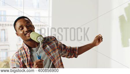 Happy African American Repairman Having Fun Singing On Roller Brush During Home Renovation. Apartmen