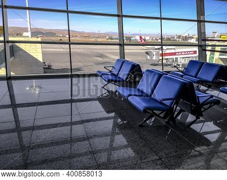 Turkey, Ankara - October 24, 2019: Blue Seats Against The Background Of The Runway Outside The Windo