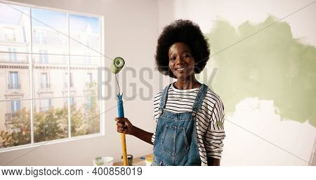 Portrait Of Smiling Happy Young African American Woman Looking At Camera Holding Painting Roller Bru