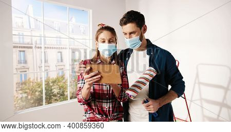 Portrait Of Happy Caucasian Young Married Couple Man And Woman In Masks Standing In Apartment Typing